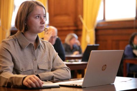 Bilde av Therese Hugstmyr Woie i rettsalen i Høyesterett. Hun sitter ved en pult og leser saksdokumenter på datamaskinen.
